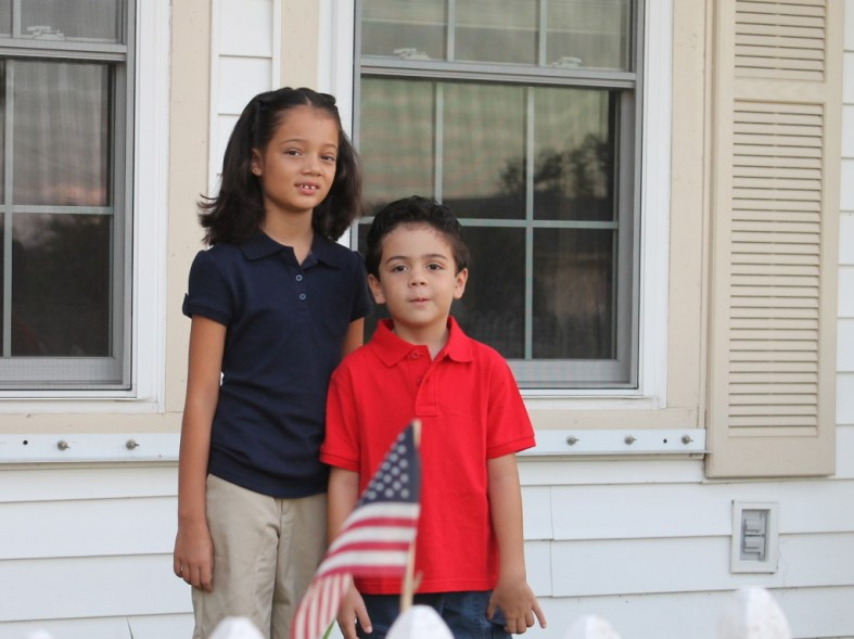 back to school, boy and girl in uniform with american flag