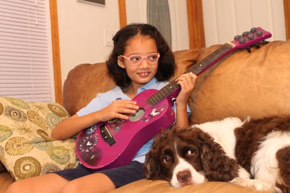 girl playing guitar with her dog