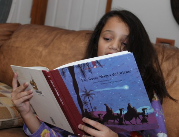 Girl reading a Dia de Reyes book