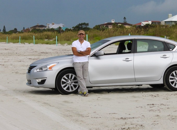 Latino man with car at the beach