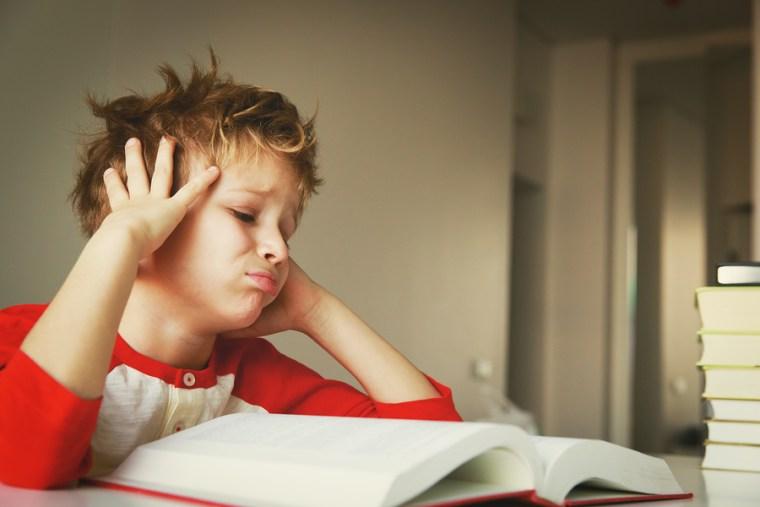 a little boy struggling with homework