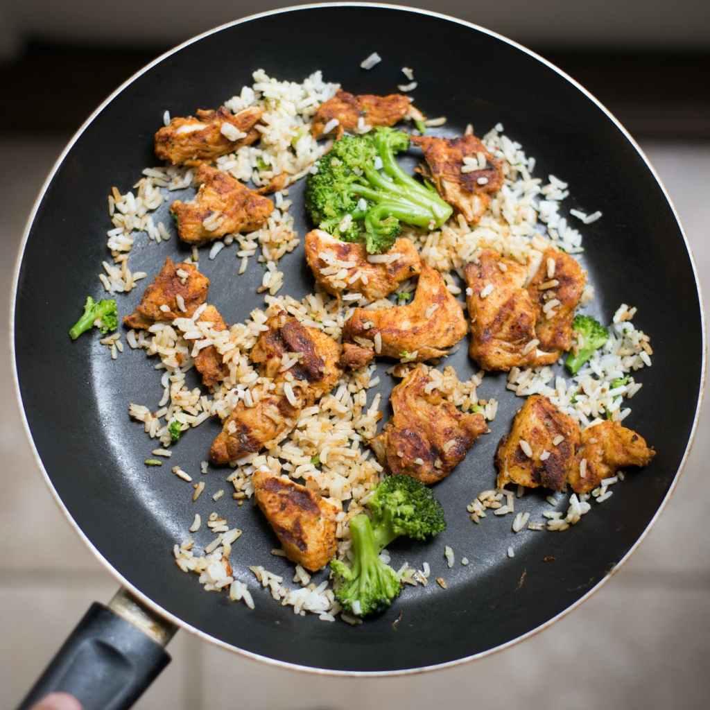 white rice chicken and broccoli on black non stick pan