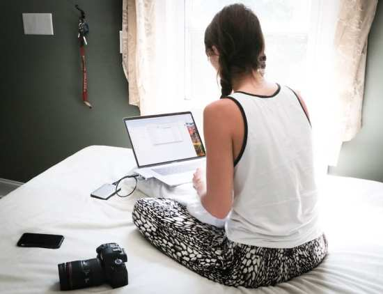 teen on computer in bed