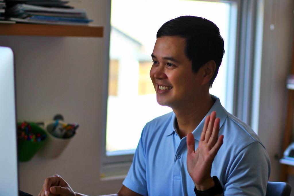 man waving at camera online networking