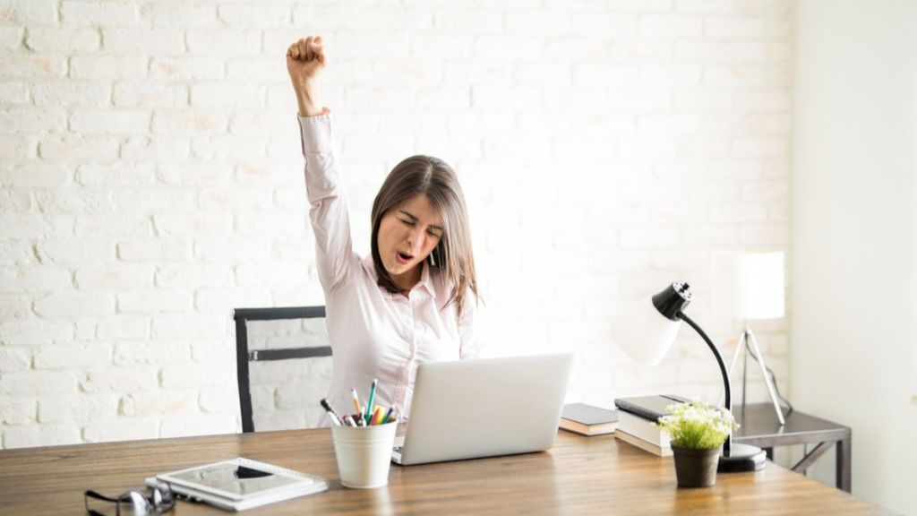 woman sitting at computer with fist up