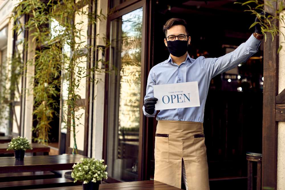 small business owner holding open sign in front of cafe