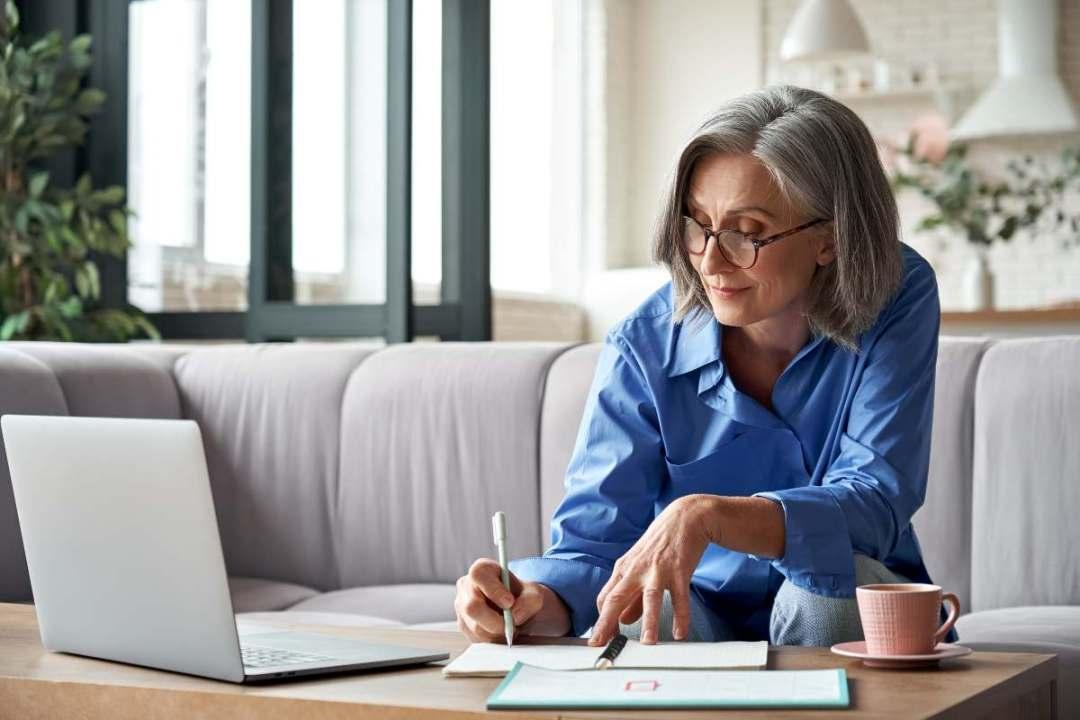 older woman studying at laptop