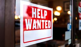 red help wanted sign on small business door