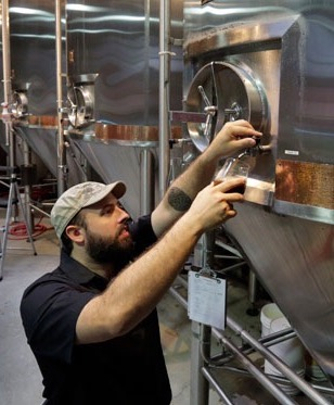 In this July 1, 2013 photo, Production Manager James Valm takes a sample from a fermentation vessel at the Brooklyn Brewery, in the Williamsburg section of the Brooklyn borough of New York. In rundown urban neighborhoods across the country, craft breweries helped transform the neighborhoods around them, drawing young new residents and other small businesses.  (AP Photo/Richard Drew)
