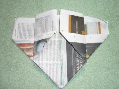 Die obere Schicht Papier wird auf jeder Seite an die Mittelfalz gefaltet