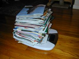 Catalogs piled up on a scale.  Click here to see proof of the weight!