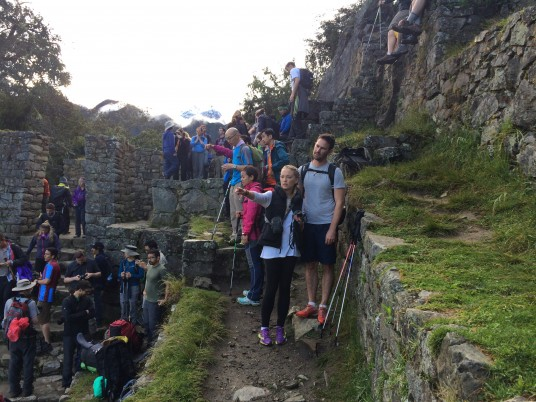 Hikers gather at the Sun Gate where we can first see Machu Picchu