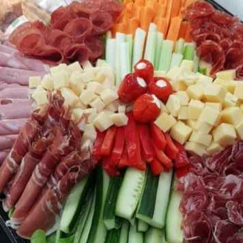 A colourful platter of vegetable sticks, rolled ham, salami and cubes of cheese.
