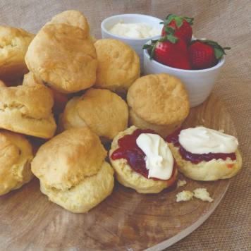 A wooden platter with a pile of freshly baked scones with jam and cream on a couple of them.