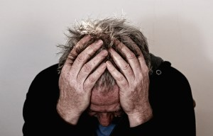 A man holding his head with both hands, regretting he did not call reputable movers Holden MA