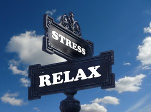 "Two signs, one saying ""stress"", the other one saying ""relax"" and a blue sky in the background"