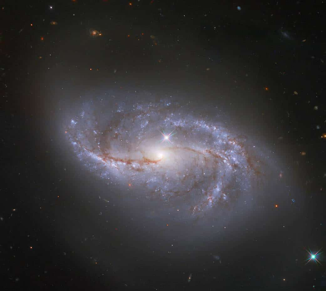 Looking deep into the Universe, the NASA/ESA Hubble Space Telescope catches a passing glimpse of the numerous arm-like structures that sweep around this barred spiral galaxy, known as NGC 2608. Appearing as a slightly stretched, smaller version of our Milky Way, the peppered blue and red spiral arms are anchored together by the prominent horizontal central bar of the galaxy. In Hubble photos, bright Milky Way stars will sometimes appear as pinpoints of light with prominent lens flares. A star with these features is seen in the lower right corner of the image, and another can be spotted just above the pale centre of the galaxy. The majority of the fainter points around NGC 2608, however, lack these features, and upon closer inspection they are revealed to be thousands of distant galaxies. NGC 2608 is just one among an uncountable number of kindred structures. Similar expanses of galaxies can be observed in other Hubble images such as the Hubble Deep Field which recorded over 3000 galaxies in one field of view.