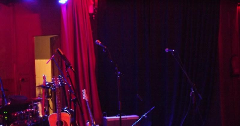 Guitarras, batería y microfonos en un escenario