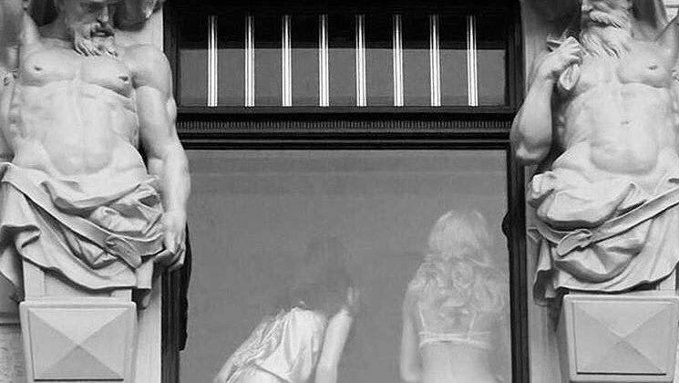 Dos estatuas de Atlantes mirando hacia una ventana en la que se ve a dos mujeres de espaldas en ropa interior