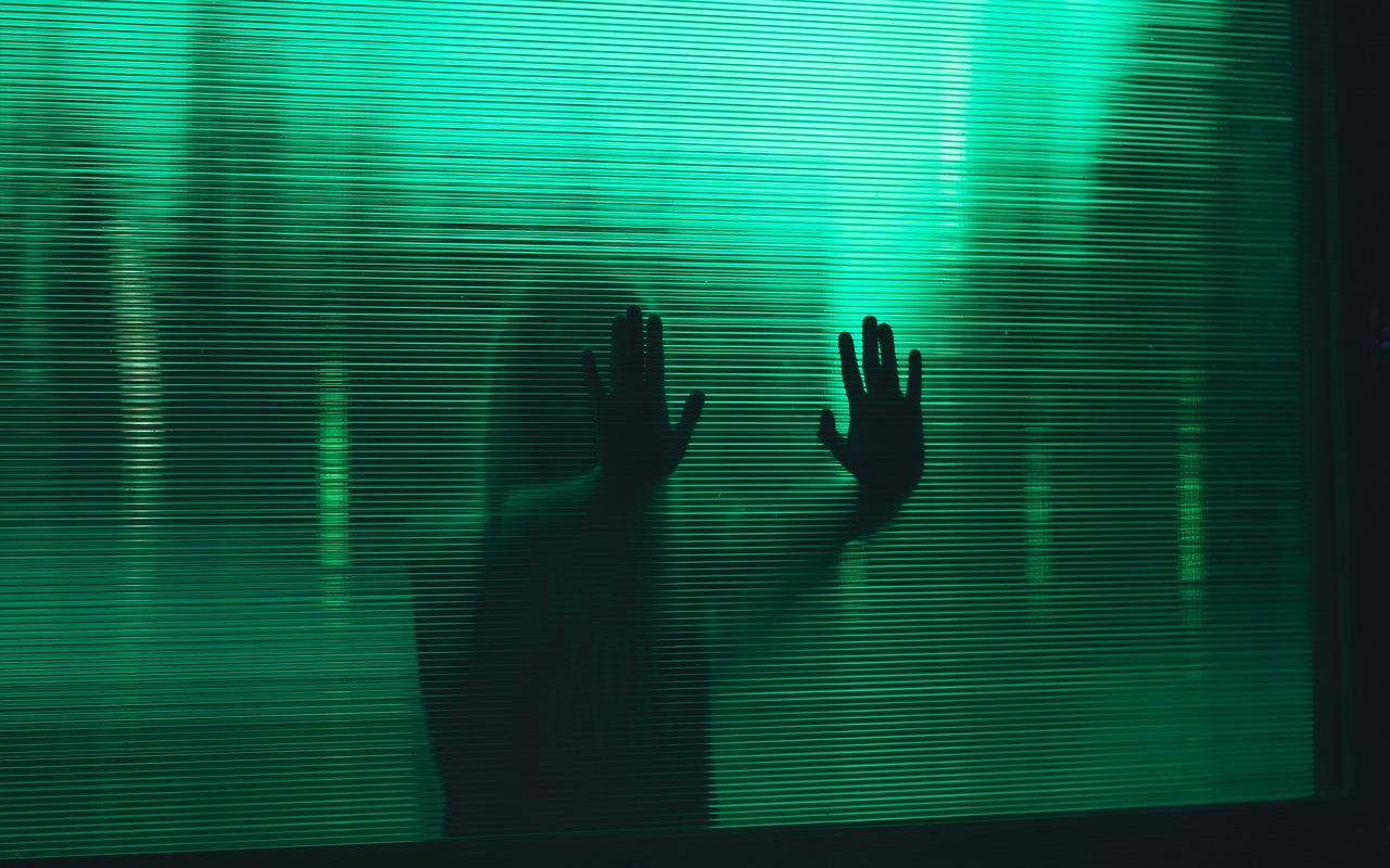 una persona a contraluz apoyando las manos en un cristal, todo ello en tonos verdosos