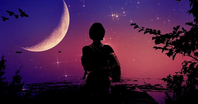 Una mujer de espaldas a contraluz frente a un cielo nocturno azulado con una luna en cuarto menguante