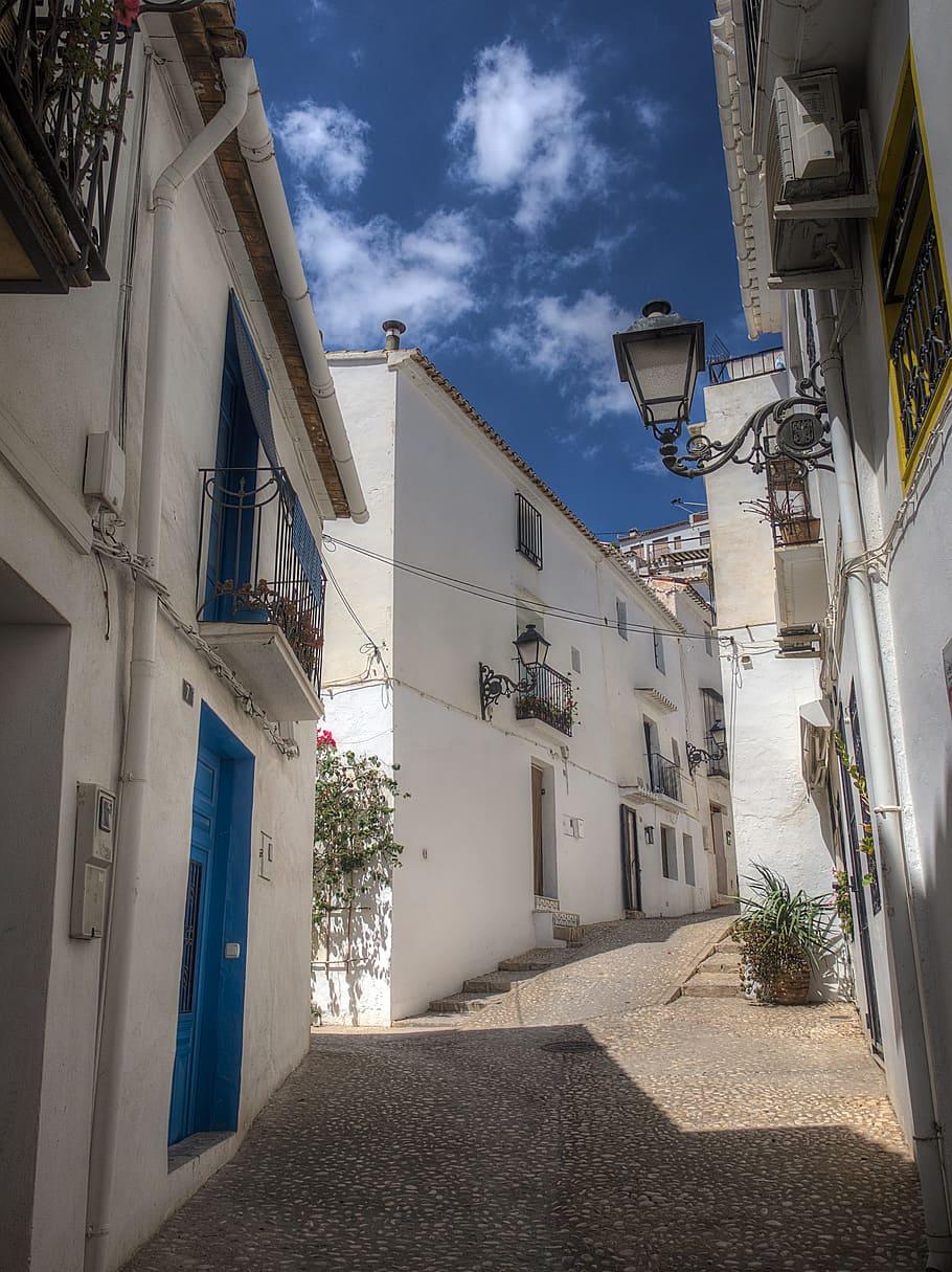 Una calle de un pueblo de fachadas blancas y puertas azules