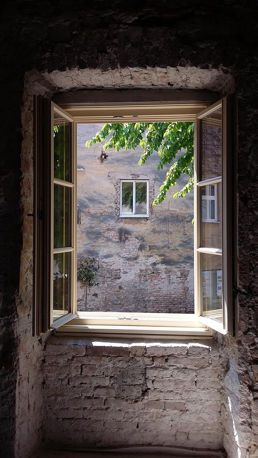 Una ventana de madera abierta de par en par