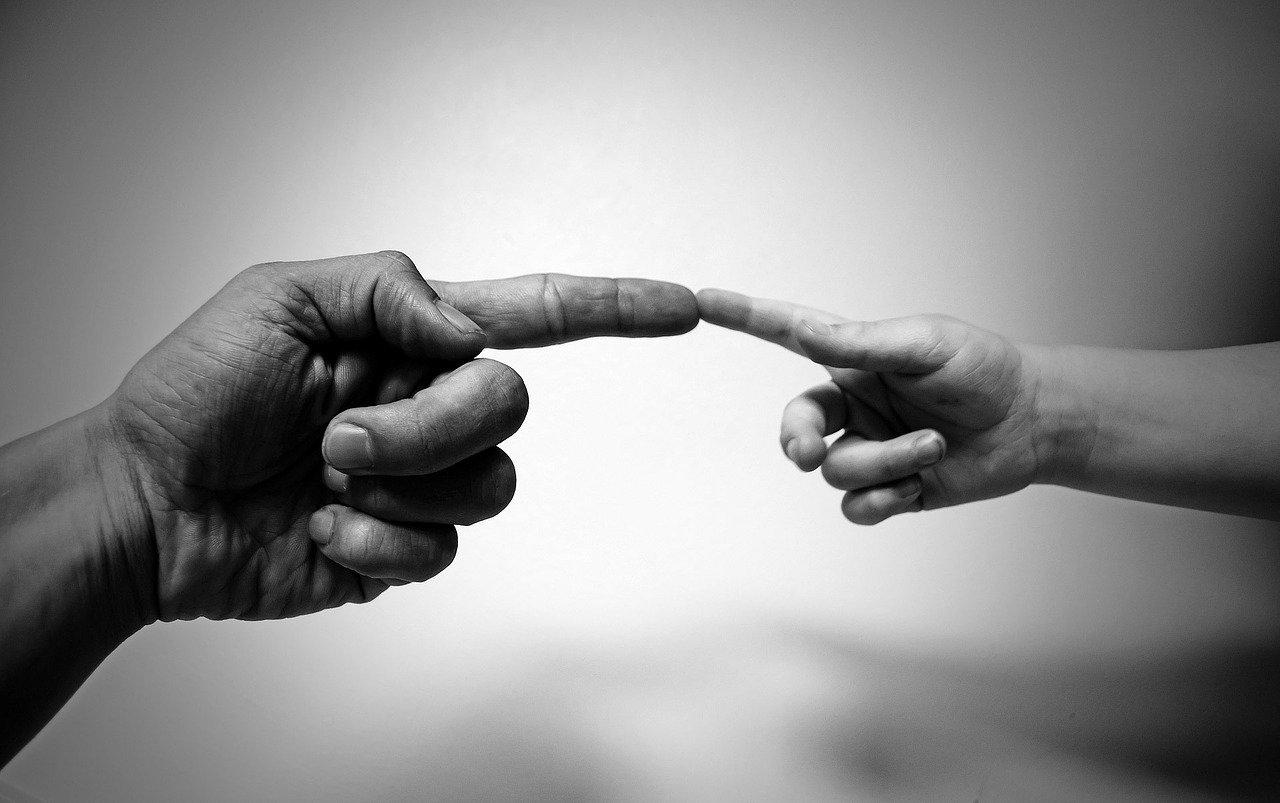 Dos manos una de adulto y otra de niño tocandose por los dedos indices como en la imagen de la capilla sixtina. https://pixabay.com/es/photos/alinear-los-dedos-dedos-%C3%ADndices-71282/