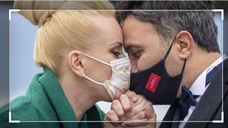 Beso de una pareja con mascarillas