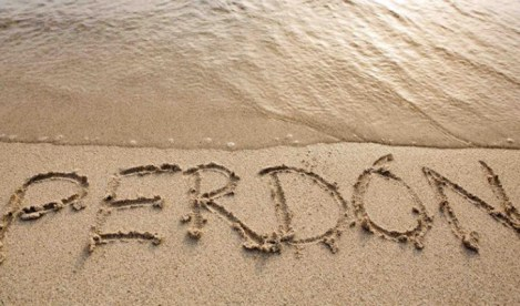 La palabra perdón escrita sobre la arena de la playa con una ola a punto de empezar a borrarla