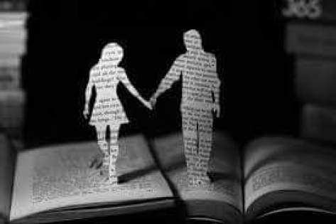 la silueta de un hombre y una mujer de la mano recortados de un libro.