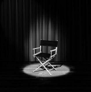Una silla tipo director en medio de un escenario iluminado por un foco cenital en un fotografía en blanco y negro