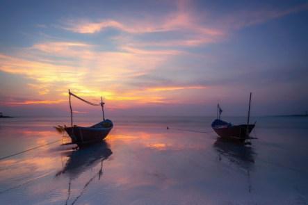 Dos barcas varadas sobre una playa ligeramente cubierta de agua durante un bello atardecer de tonos arrebolados
