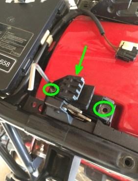 Schrauben der Sitzbankhalterung lösen und diese abnehmen. Der grüne Pfeil zeigt die zweite Schraube der Verriegelung.