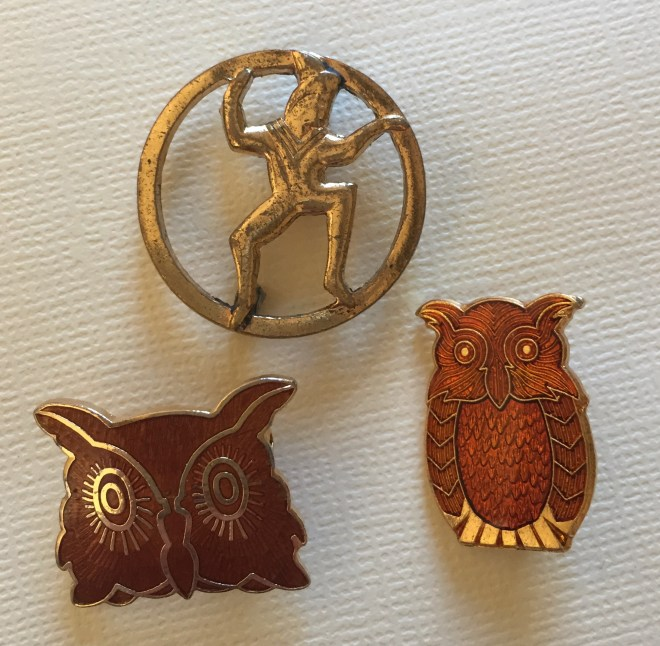 gold circle pin with a Brownie elf and two enameled brown owl pins