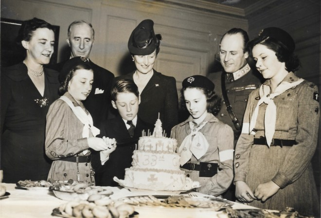 A group of well dressed children and adults prepare to cut a birthday cake.
