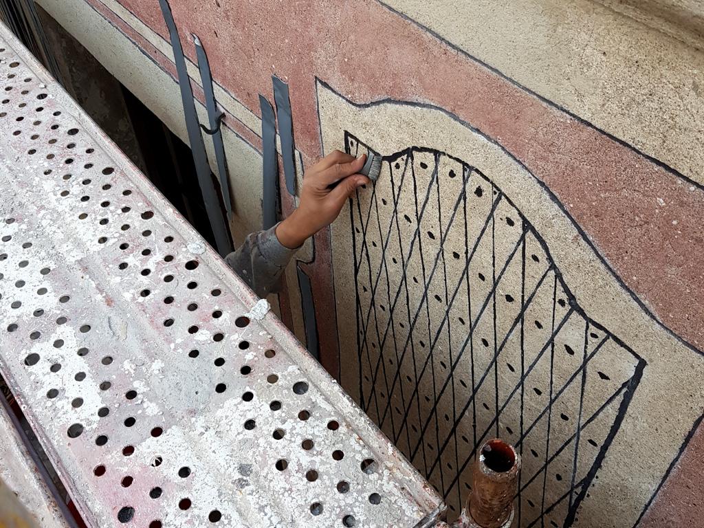 Mano del artesano recuperando los esgrafiados
