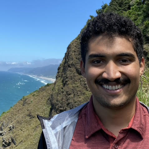 Smiling man in red shirt standing above sea cliff
