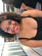 Black woman with glasses sitting outside in black outfit smiling