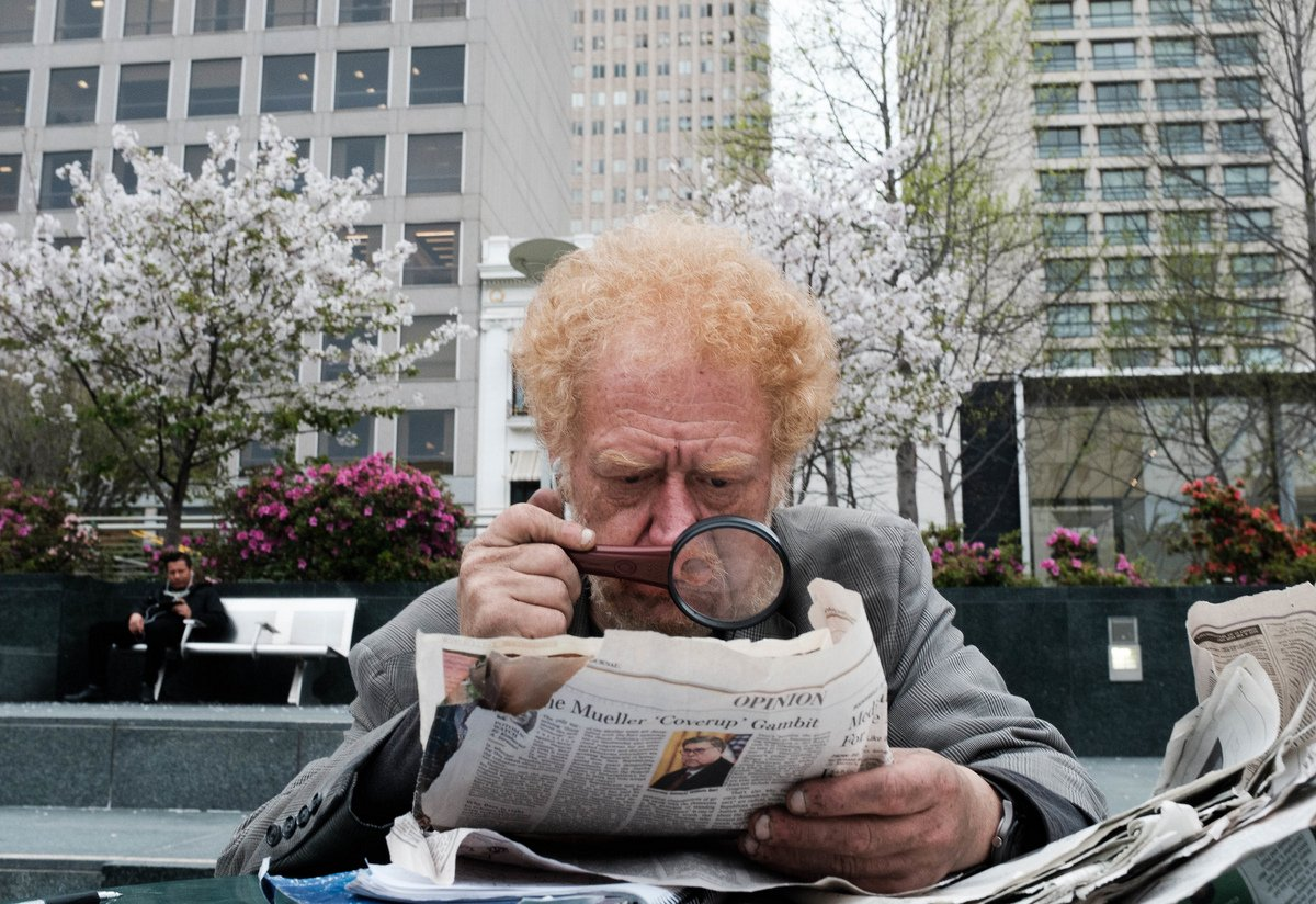 A man sits outside reading a newspaper with a magnifying glass