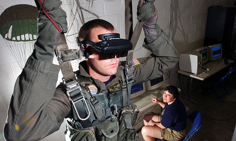 021115-N-5862D-001 Aboard Naval Air Station (NAS) Pensacola (Nov. 15, 2002) -- Hospital Corpsman 2nd Class Tim Sudduth, from Vashowish, Wash., demonstrates the Virtual Reality (VR) parachute trainer, while Aviation Survival Equipmentman 1st Class, Jackie Hilles, from Ekland, Penn., controls the program from a computer console. Students wear the VR glasses while suspended in a parachute harness, and then learn to control their movements through a series of computer-simulated scenarios. The computer receives signals from the student as they pull on the risers that control the parachute. The VR trainer also teaches aircrew personnel how to handle a parachute in different weather conditions and during possible equipment malfunctions. Navy and Marine Corps aviators receive state of the art training at the Naval Survival Training Institute. U.S. Navy photo by Chief Photographer's Mate Chris Desmond. (RELEASED)