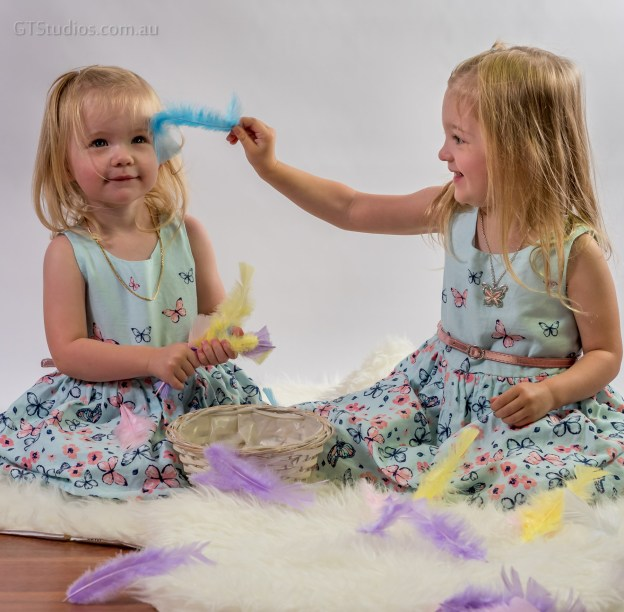 Tickled - beautiful young girls with feathers on rug