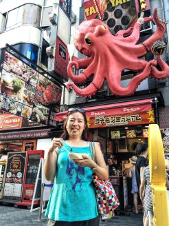 4. Mom posing with her takoyaki, a ball-shaped snack made of flour-based batter and filled with diced tako – or octopus – in front of the stall in Dōtonbori.