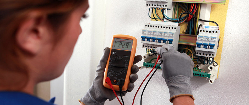 female technician with multi-meter troubleshooting control