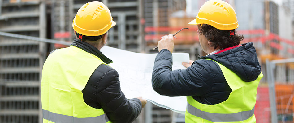 two construction men looking at plans