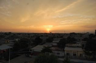 Sonnenuntergang auf dem Dach der Musikschule. Der Guasmo versinkt in Orange und Schwarz