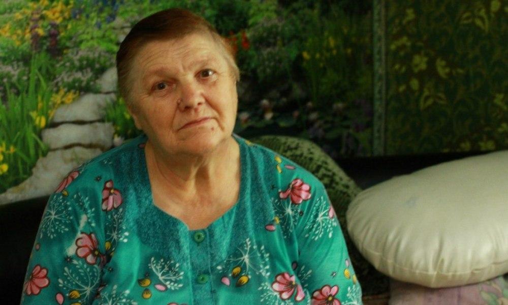 Бабушка в зеленом платье сидит на фоне зеленой стены