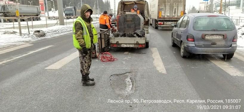 Рабочие в оранжевом и желтом жилетах стоят около машины на улице и чинят яму