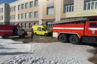 Желтая машина скорой помощи и красная пожарная машина стоят на улице около трехэтажного здания