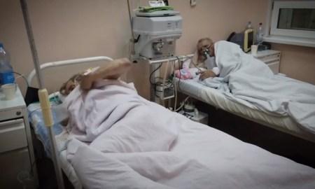 в палате на больничных кроватях лежат под белыми одеялами два пациента